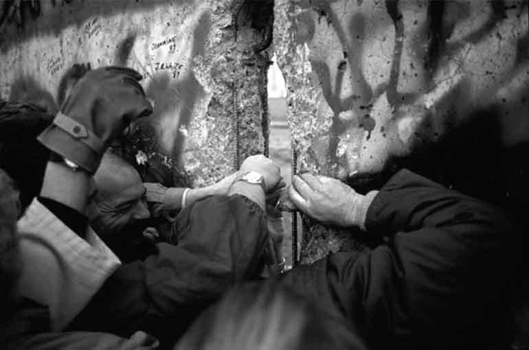 Berlin Duvarı'ndaki bir gedikten bakan insanlar
